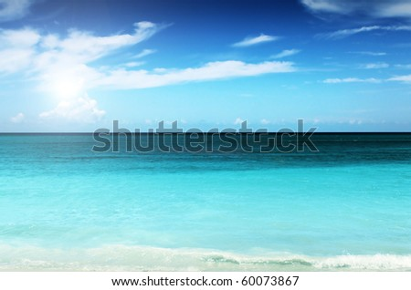 Landscape photo of a bright blue sky with clouds above a tropical ocean and coastline