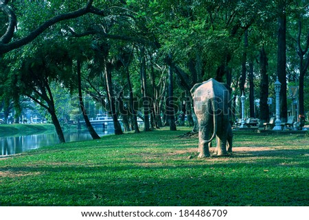 Landscape photo of an outdoor natural park in Cambodia, with fake elephant walking among trees - stock photo