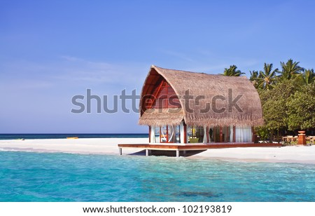 Landscape photo of beach house in Maldive ocean with blue sky - stock photo