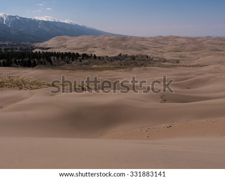 Landscape photo of Great Sand Dunes National Park shows vast dunes with rocky mountains in background - stock photo