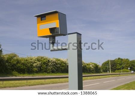 Landscape photo of road and yellow speeding camera. - stock photo
