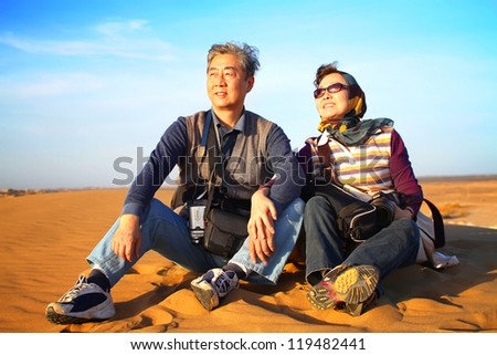 Landscape photo of senior couple sitting in desert enjoying the sunset - stock photo