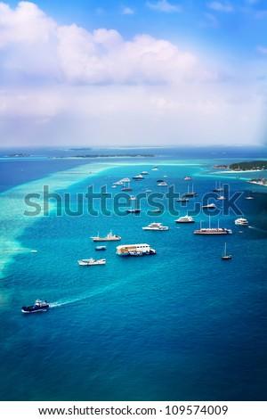 Landscape photo of Ships in ocean near beach in Maldive Island - stock photo