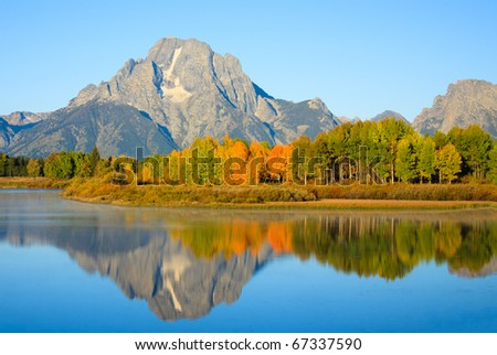 Landscape photograph of morning light shining on Mount Moran and fall trees reflecting in the Snake River at Oxbow Bend.  Grand Teton National Park, Wyoming
