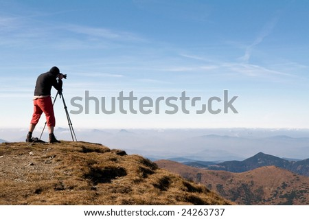 landscape photographer in the mountains taking pictures - stock photo
