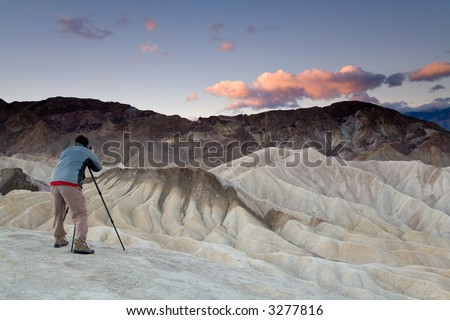 Landscape photographer taking pictures at sunrise in Death Valley national park in California. - stock photo