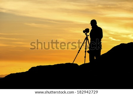 Landscape photographer with a tripod mounted camera profiled against the sunset. - stock photo