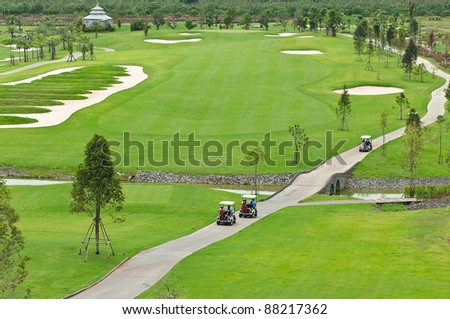landscape picture of a golf court with golf cart - stock photo