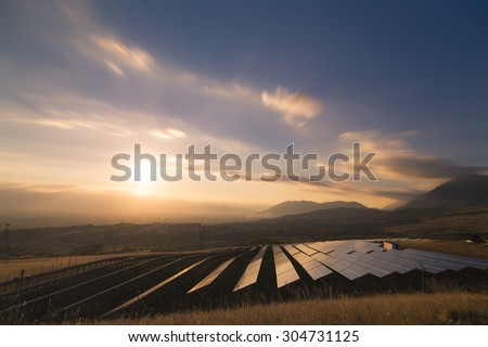 Landscape picture of a solar plant that is located inside a valley surrounded by mountain during the sunset. - stock photo