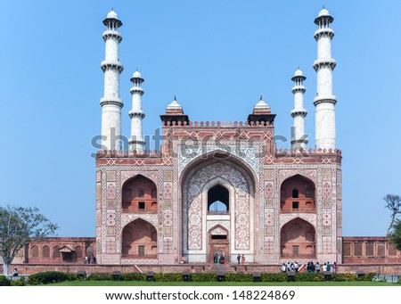 Landscape picture of Akbar's Tomb and its four minarets in India's Agra. Colorful decorations on red sandstone, white minarets against blue skies over green lawn.