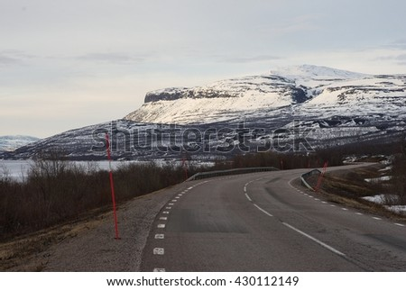 Landscape Picture of asphalt road in the Lapland in north Sweden Road from Kiruna to Narvik in Norway along big lake Tornetrask and mountains. Picture taken in spring, country still under snow and ice - stock photo