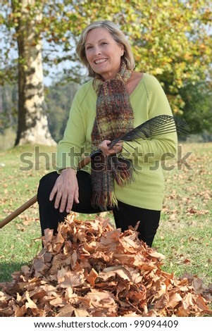 Landscape picture of woman picking up litter - stock photo