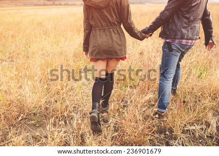 Landscape portrait of young beautiful stylish couple sensual and having fun outdoor. Film effect - stock photo