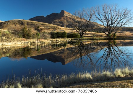 Landscape reflection in a dam in the Drakensberg Mountain range. There are rural dwellings in the distance. - stock photo
