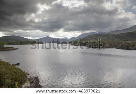 Landscape scene on the west coast of Ireland in County Killarney looking across Loch Guitane at dusk with dramatic broken storm clouds and reflections in the lake.