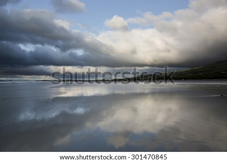 Landscape  scene on the west coast of Ireland with light shining through broken storm clouds and blue sky and reflections on a deserted endless sandy beach during stormy weather in summer in  Kerry. - stock photo
