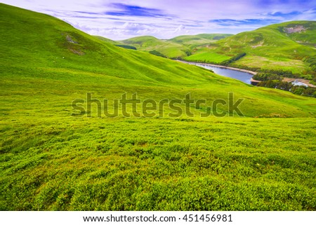 Landscape scenery of green valley, hill, river and cloudy blue sky. Pentland hills, Scotland - stock photo