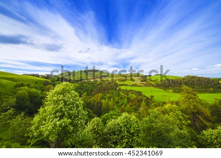 Landscape scenery of green valley with trees, hill and cloudy blue sky. Pentland hills, Scotland - stock photo