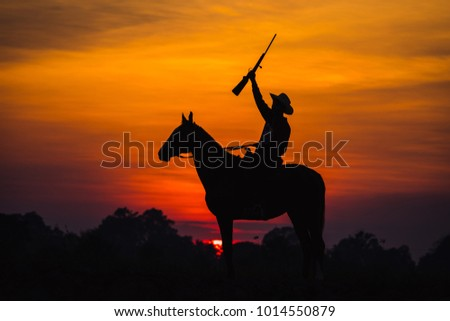 landscape silhouette cowboy horse carrying riding a gun the backdrop is the sun