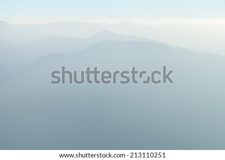 Landscape. Silhouettes of mountain slopes in the haze. - stock photo