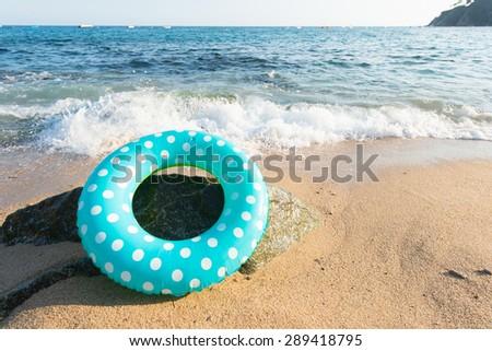 Landscape Spanish Costa Brava beach with inflatable toys - stock photo