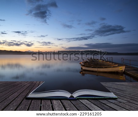 Landscape sunrise over still lake with boats on jetty conceptual book image - stock photo