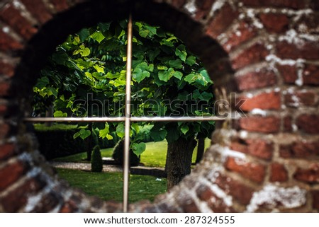 Landscape through round window on brickwall - stock photo