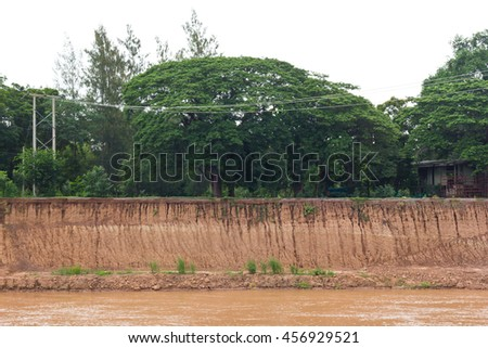 Landscape trees beside the road with soil erosion near the river shore slide with housing and utility poles. - stock photo