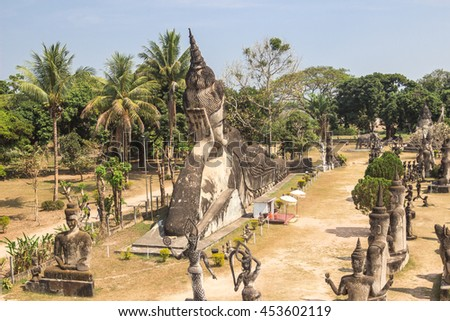 Landscape view at gigantic Reclining Buddha ancient statue among sculptures of hindu and buddhism gods in Buddha Park, Vientiane, Laos - stock photo
