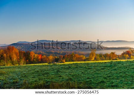 Landscape view of a morning sunrise during fall foliage season, Stowe, Vermont, USA. - stock photo