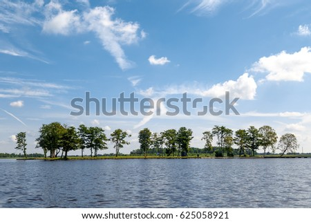 Landscape view of big lake with trees and field around, on cloudy sky background.