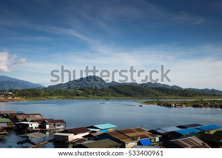 Landscape view of great lagoon in front of a mountain with a village on bottom and a blue sky