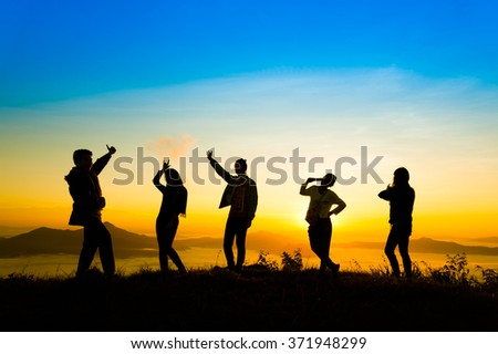 Landscape view of sunrise on misty  mountain hills with women and man silhouette, phatang mountain Chiangrai Thailand