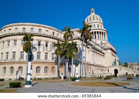 Landscape view of the Capitol building ( El Capitolio )  in Havana with a beautiful blue sky and royal palm trees - stock photo