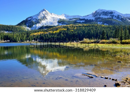 landscape view of the colorful alpine scenery, snow covered mountains and reflection in the lake during foliage season at Kebler and Ohio Passes