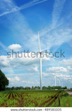Landscape view Wind Turbine farms among the fresh green corn field next to the high way contrast with white cloud and vivid blue sky color Summer time Moergestel village The Netherlands