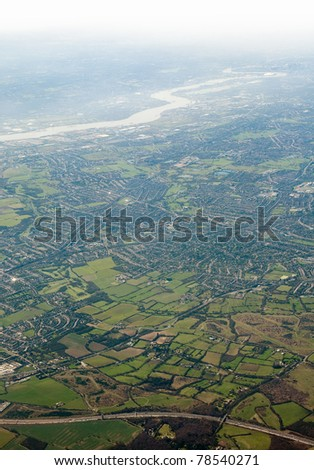 landscape viewed from airplane, photo taken near London, Themes river in distance - stock photo