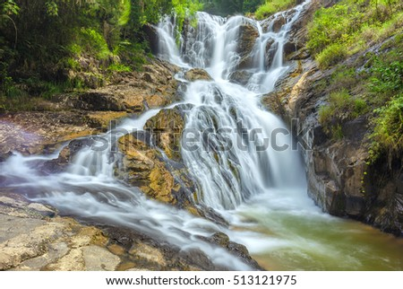 Landscape waterfall flowing into soft silk sheet in the forest create the beauty of the natural world in the wilderness. It's great to be exploring ecological tourist services there.