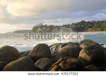 Landscape, waves smashing at rocks , sunset sky, clouds at ocean, tropical view, shoreline with hotels
