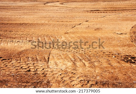 landscape wheel's trail tread in the red mud as a background - stock photo