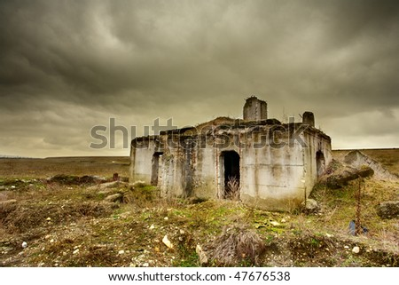 Landscape with a decrepit ruin of a building under moody sky - stock photo