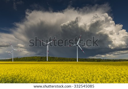 Landscape with a field of rape and wind electric-turbines.  Conceptual image illustrating production of alternative sources of energy, Europe - stock photo