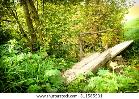 Landscape with a wooden bridge over a river  - stock photo