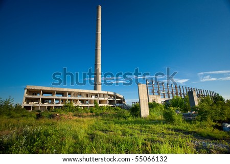 Landscape with abandoned industrial facilities under blue sky - stock photo