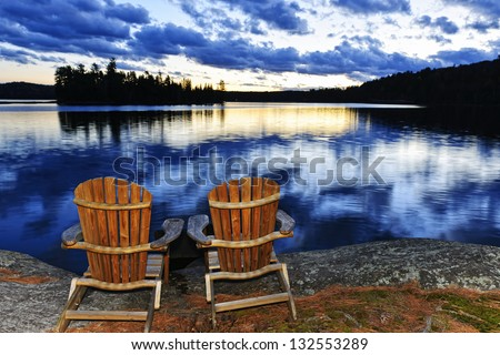 Landscape with adirondack chairs on shore of relaxing lake at sunset in Algonquin Park, Canada - stock photo