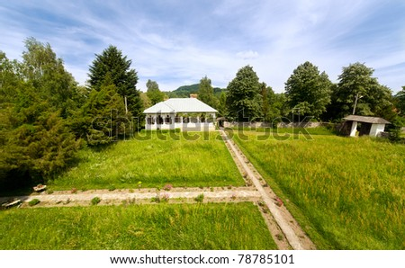 Landscape with an old Romanian house on a meadow