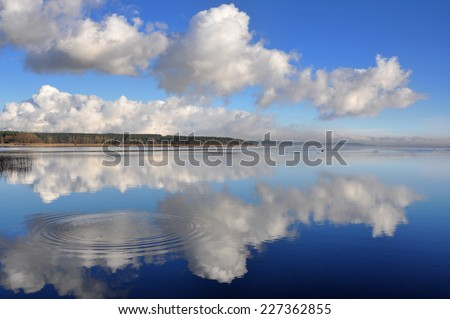 Landscape with big dark clouds.  lake reflection clouds Latvia  - stock photo