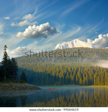 Landscape with blue sky, mountains, lake and lonely boat - stock photo