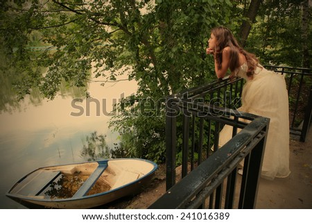 landscape with boat and pensive girl ashore calm lake, instagram image style - stock photo