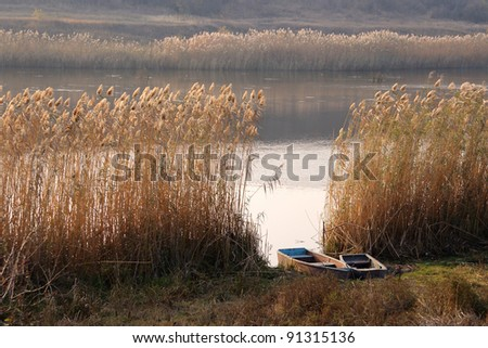 Landscape with boat in the reed on river. HDR image. - stock photo